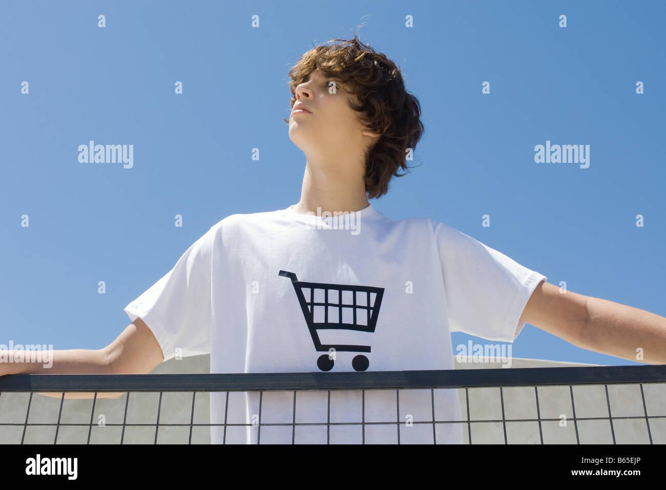 Teenage boy wearing tee-shirt printed with shopping cart, standing at railing, looking up - Stock Image