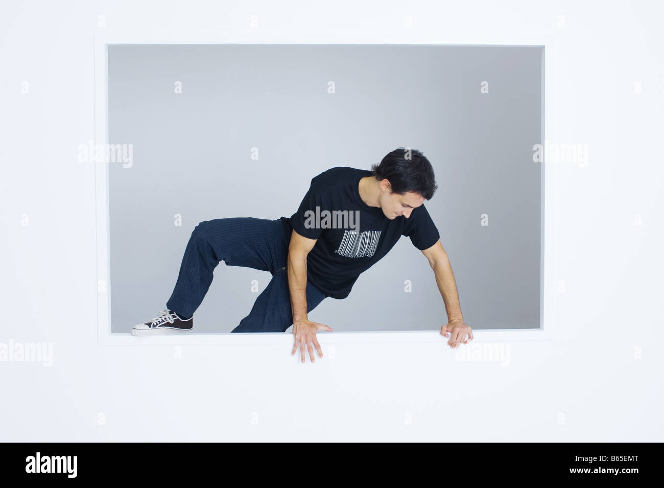 Man climbing over wall, wearing tee-shirt with bar code printed on it Stock Photo