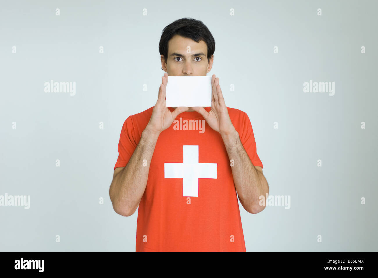 Man wearing Swiss flag tee-shirt, holding blank card in front of mouth - Stock Image