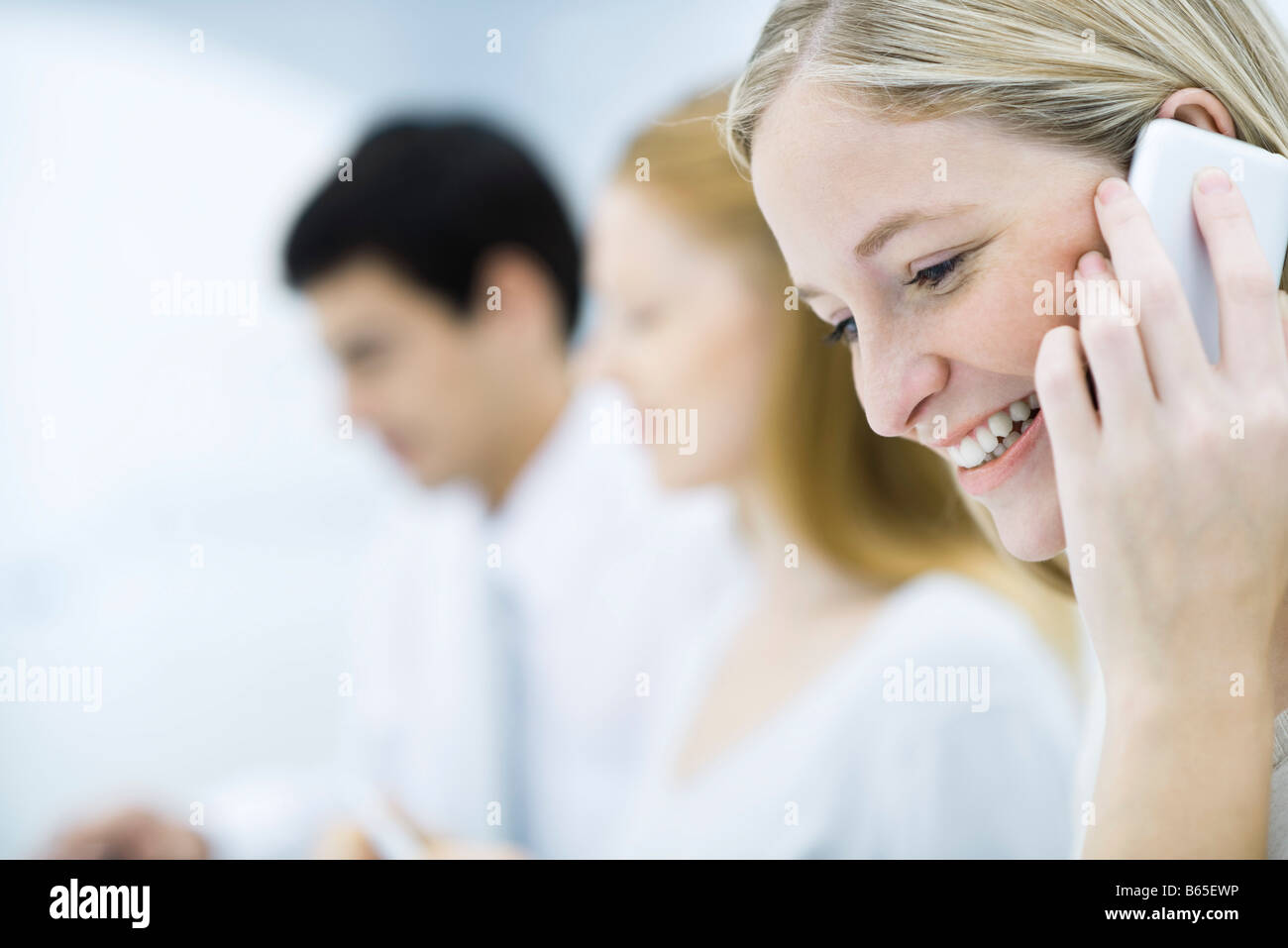 Young professional woman talking on cell phone, colleagues working in background - Stock Image