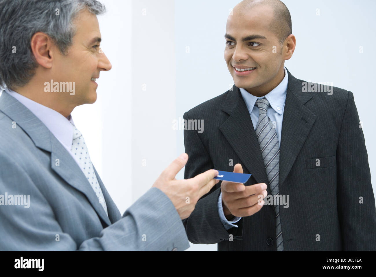 Handing out business cards stock photos handing out business cards two businessmen exchanging business card stock image colourmoves