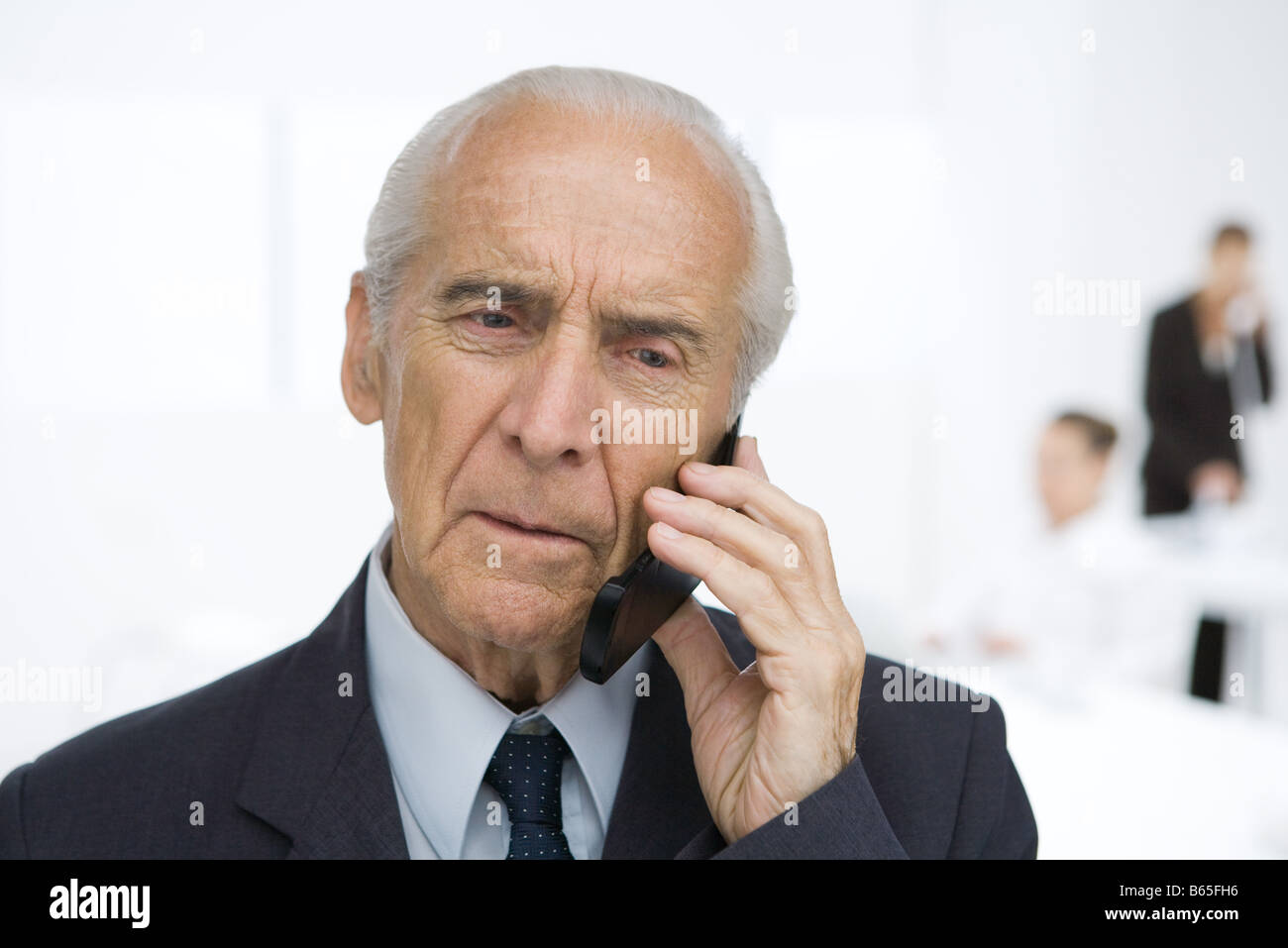 Senior businessman using cell phone, furrowing brow - Stock Image