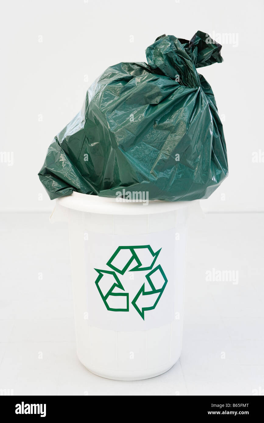 Excessively large garbage bag stuffed partially into recycling bin - Stock Image