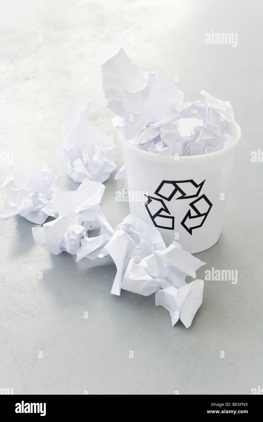 Crumpled paper overflowing recycle bin, close-up - Stock Image