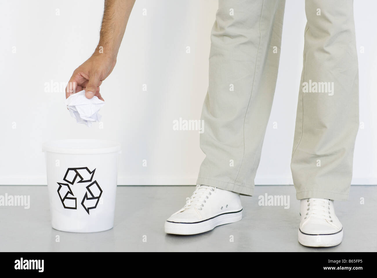 Hand placing crumpled paper into recycle bin, close-up Stock Photo