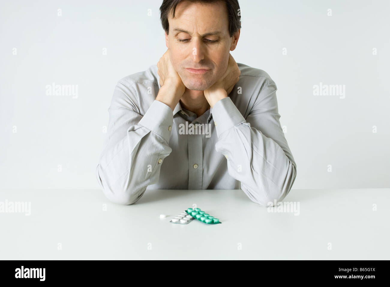 Man sitting next to pills, holding neck, looking down - Stock Image
