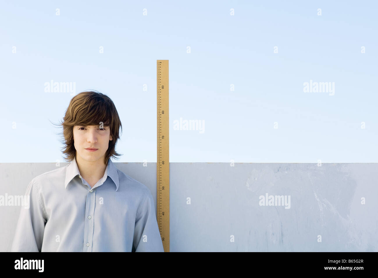 Young man measuring his height with ruler Stock Photo