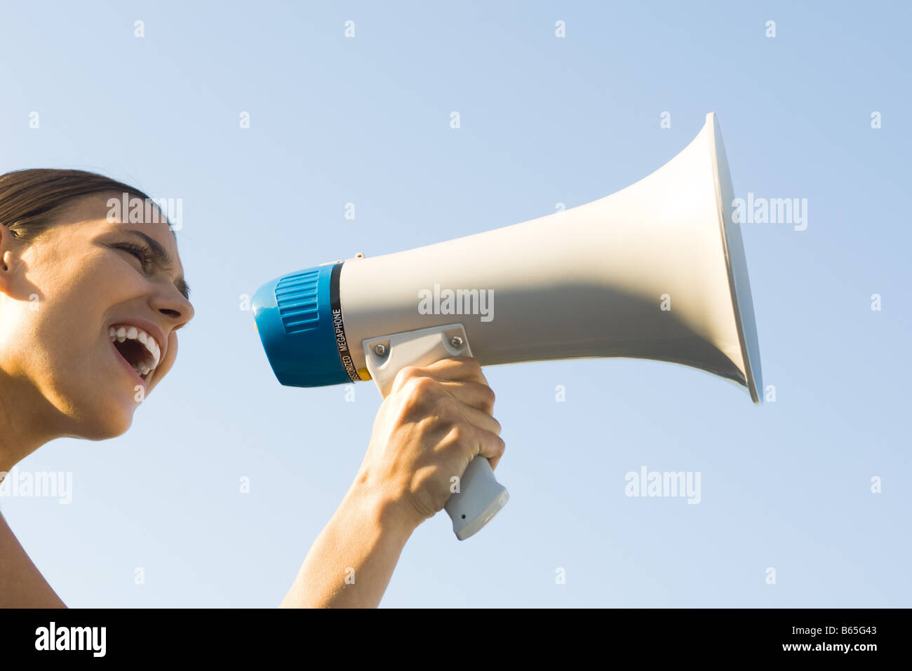 Woman shouting into megaphone, low angle view, cropped - Stock Image