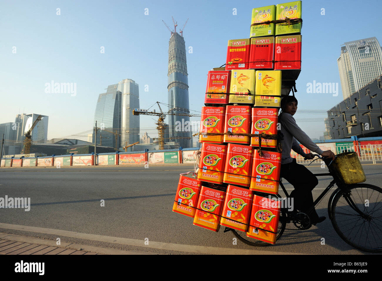 A man rides a bicycle with cooking oil past a construction site in Guangzhou, Guangdong, China. 26-Dec-2008 - Stock Image