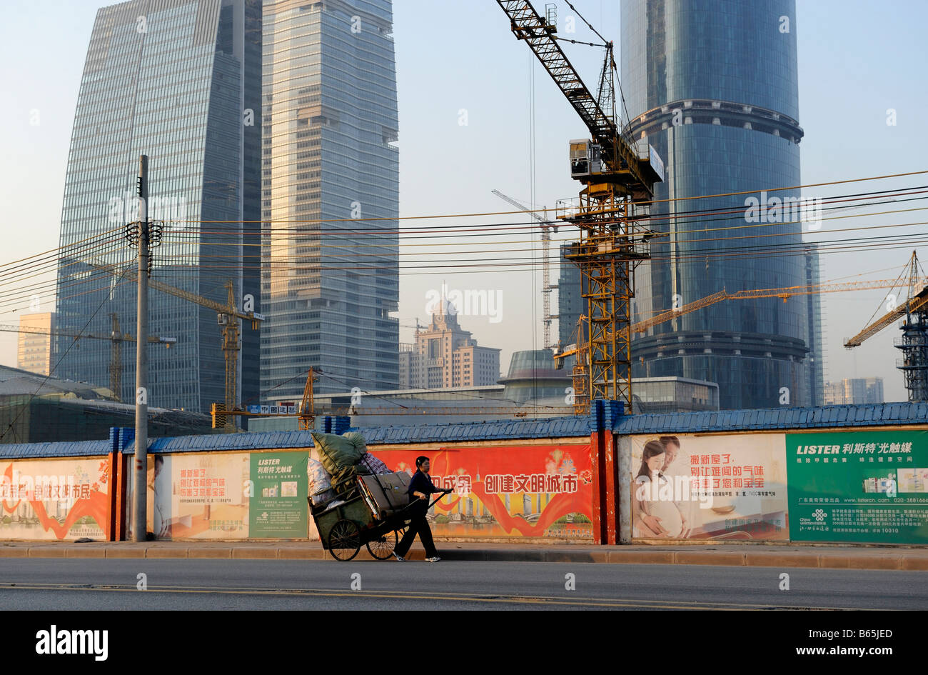 A woman transports bags and waste paper on a handcart on the pavement in front of a construction site in Guangzhou. - Stock Image