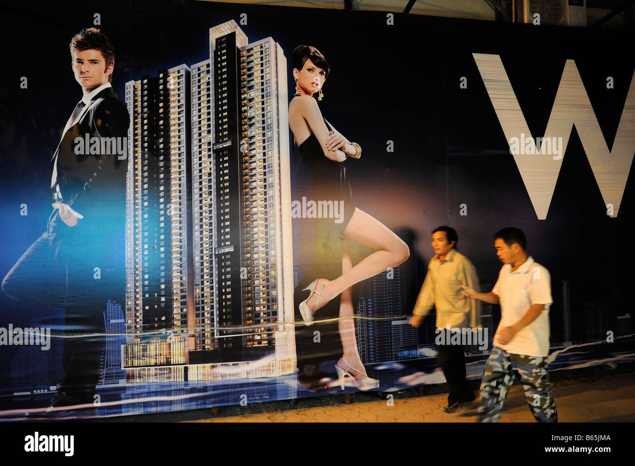 Chinese men walk past a billboard featuring a luxurious hotel being built in Guangzhou,China. 26-Nov-2008 - Stock Image