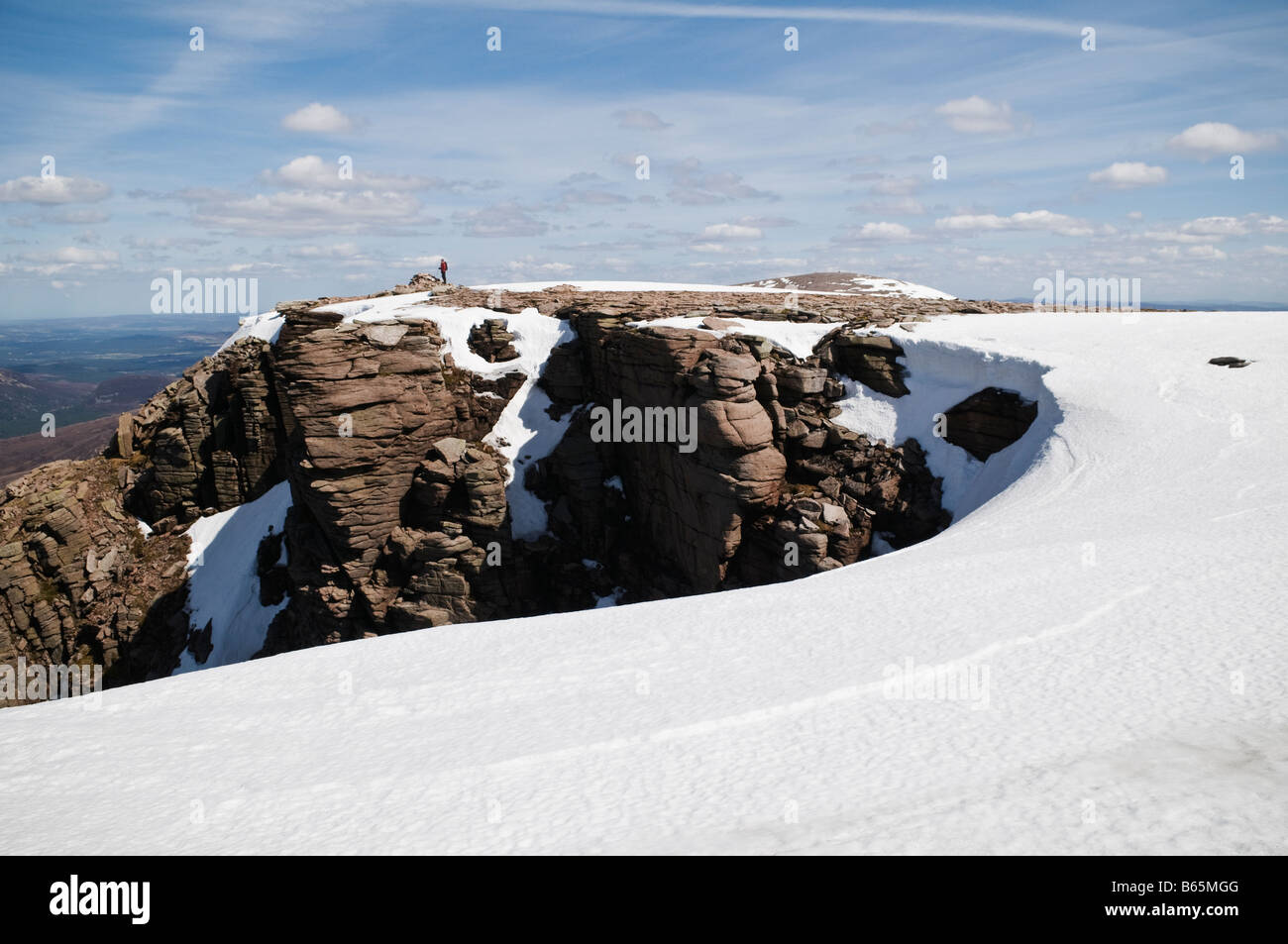 Person stands in distance on summit of Cairn Lochan in the Cairngorms Scotland - Stock Image