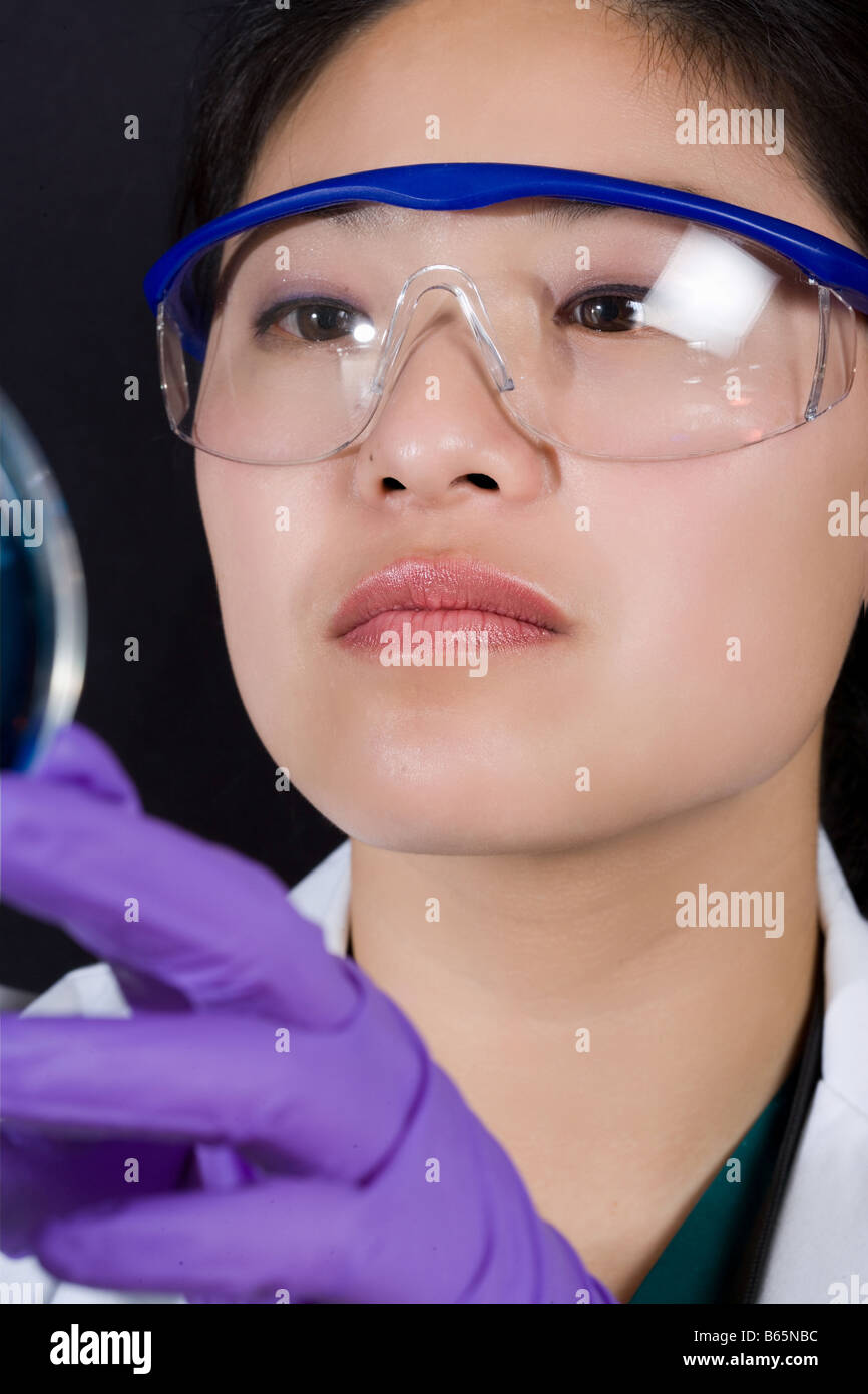 Microbiologist looks at a specimen. - Stock Image