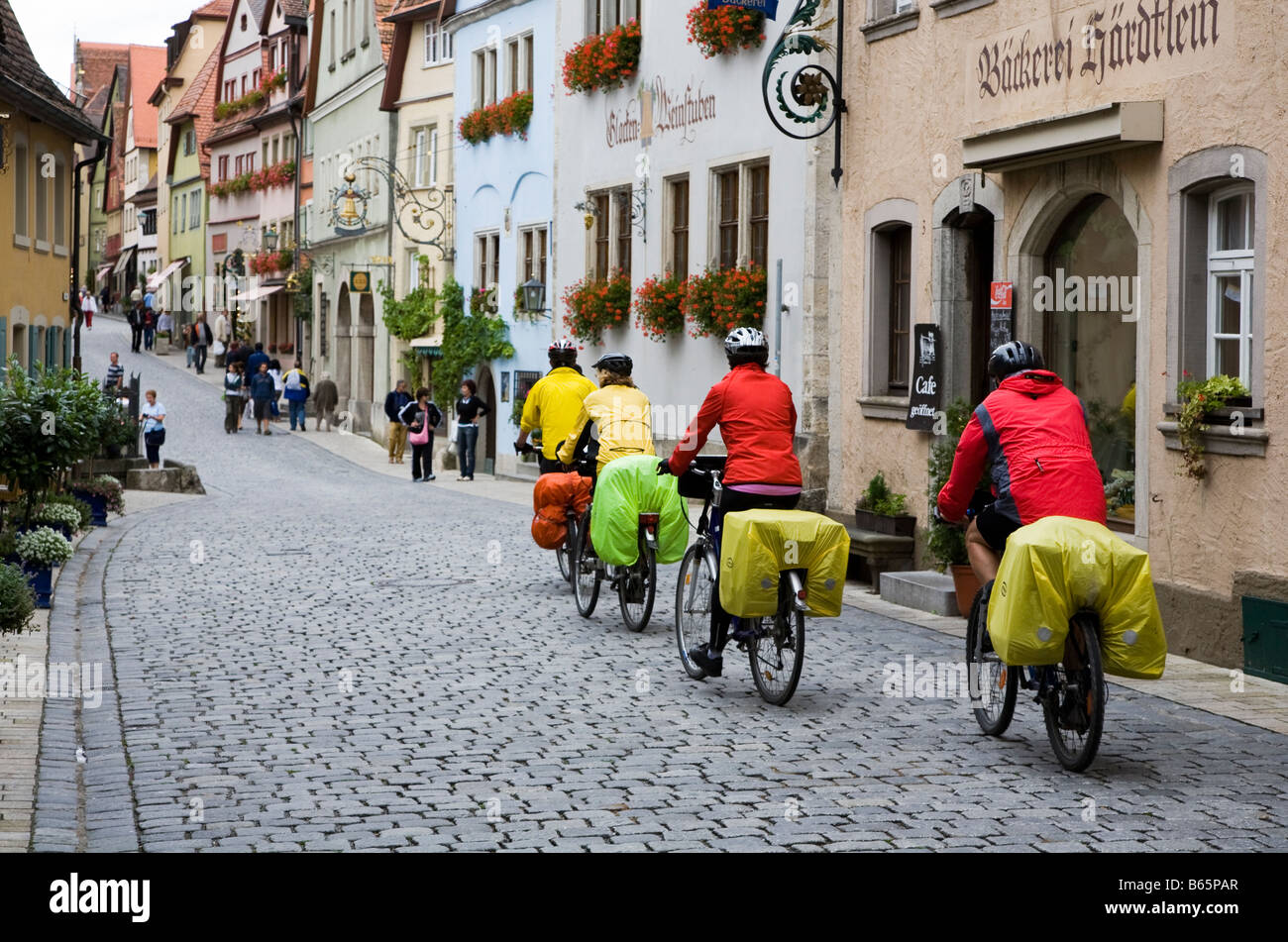 Cyclists wearing wet weather ponchos entering medieval town of Rothenburg Germany - Stock Image