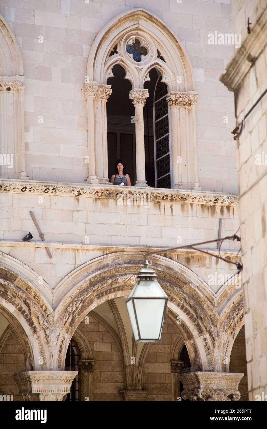 A woman looks out of an upper window in Dubrovnik's 15th Century Rector's Palace, which houses the Museum - Stock Image