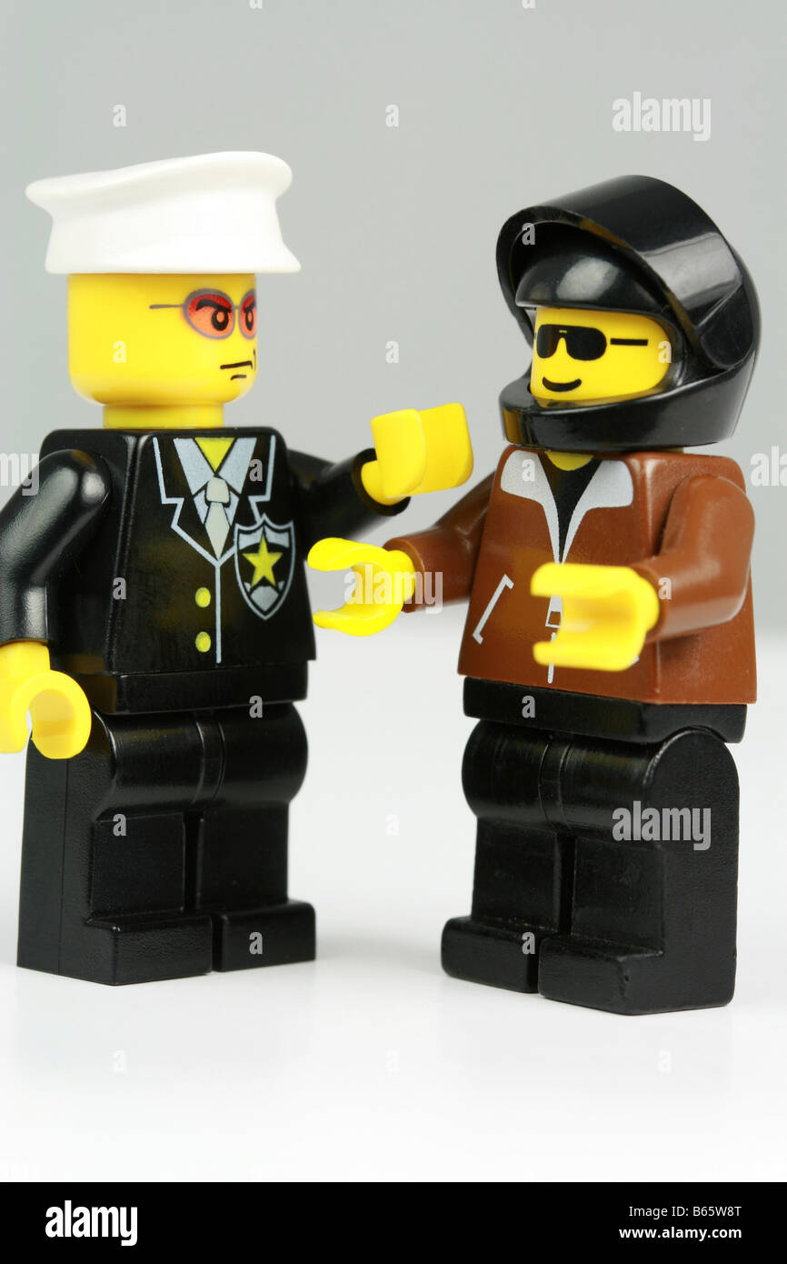 irresponsible lego motorcyclist being reprimanded by a lego policeman - Stock Image