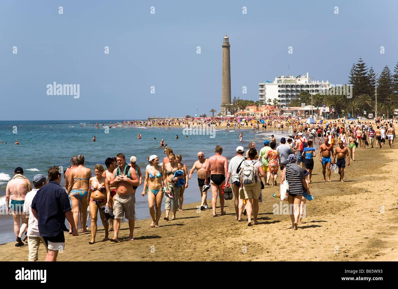 Crowds of tourists walking on beach Maspalomas Gran Canaria Spain - Stock Image