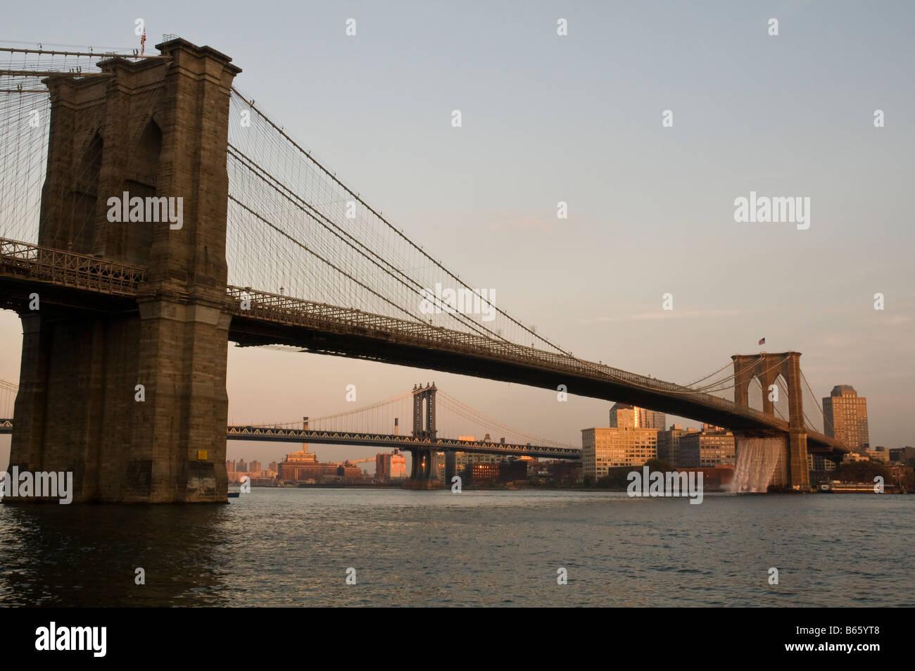 Brooklyn Bridge and New York City Waterfalls art project by Danish artist Olafur Eliasson at dusk New York USA Stock Photo