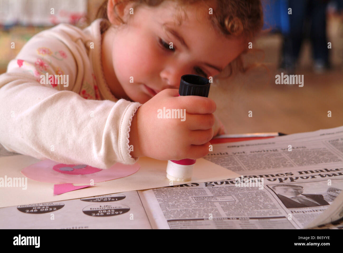 Little girl making a picture at nursery - Stock Image