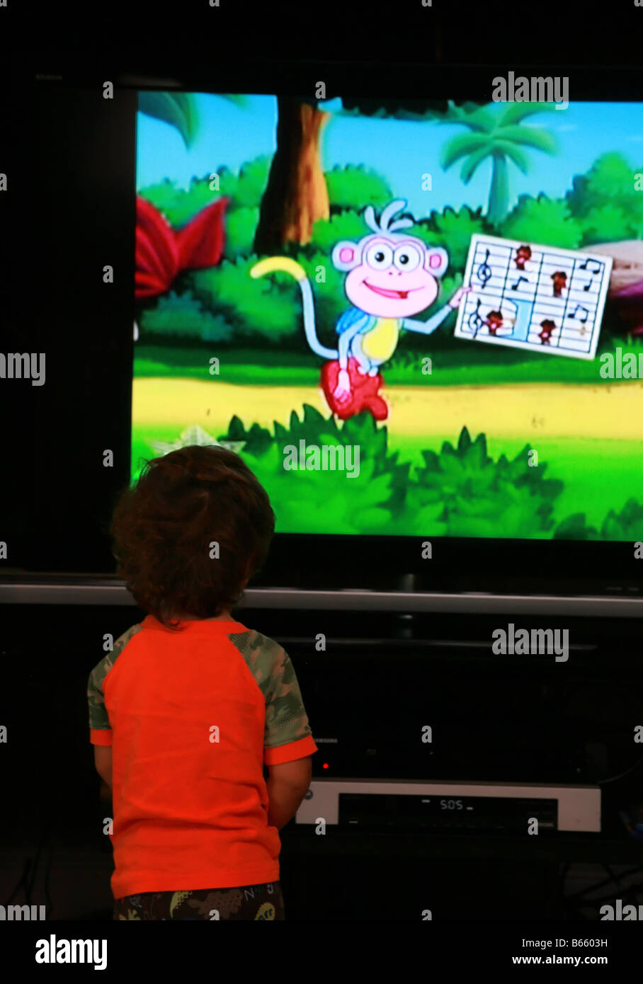 A young child watching cartoons on tv - Stock Image
