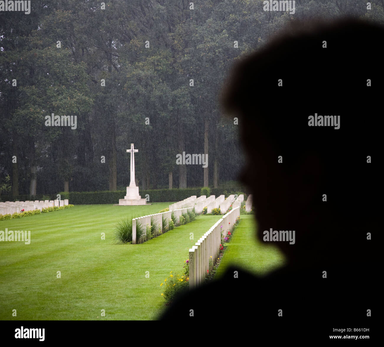 Silhouette of woman looking at war graves in the rain Arnhem cemetery Netherlands - Stock Image