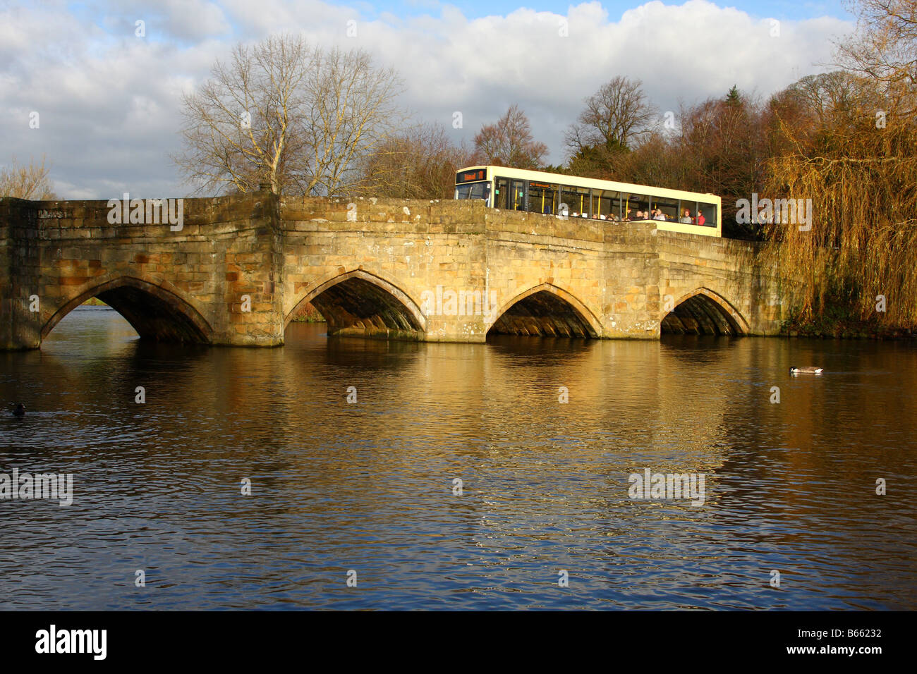A rural bus service crossing a narrow bridge over the River Wye at Bakewell, Derbyshire, England, U.K. - Stock Image