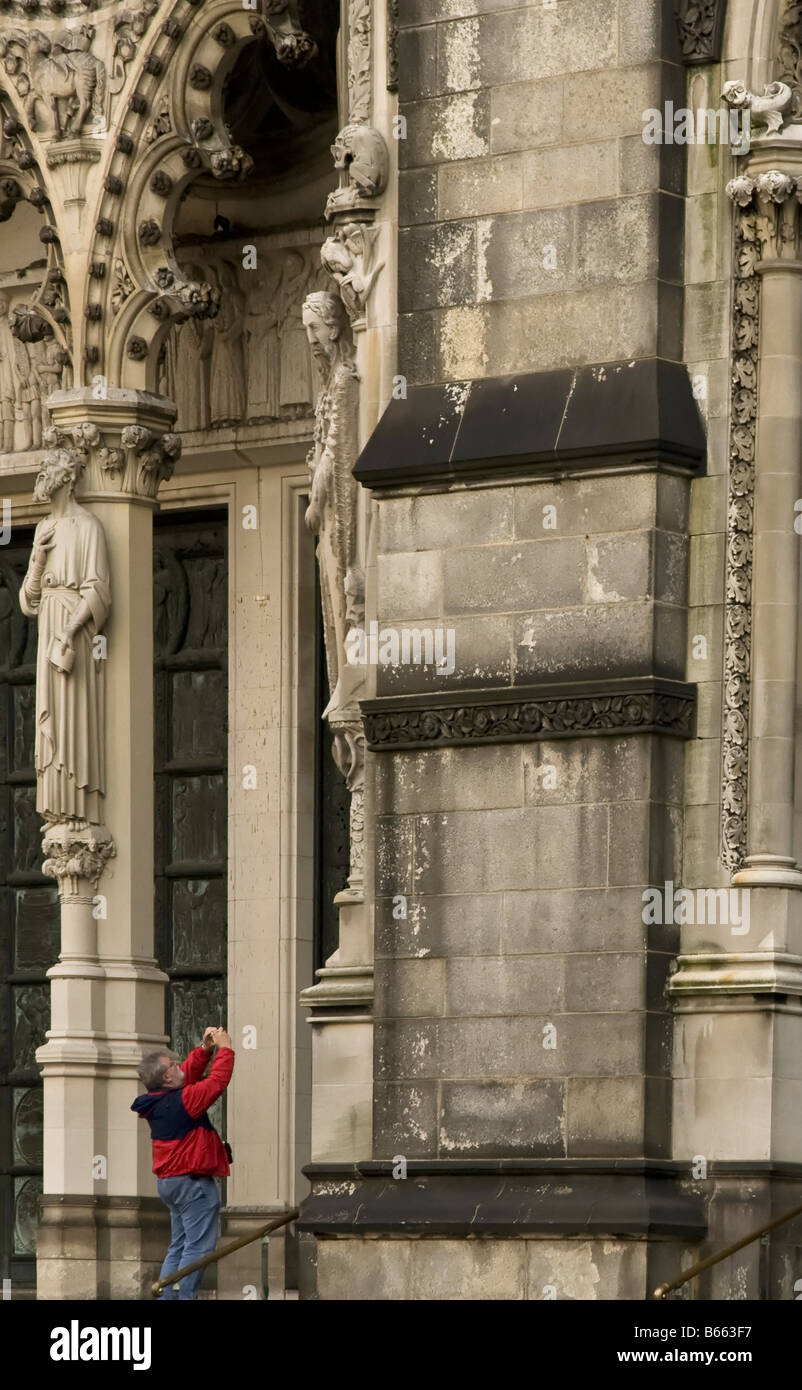 A man takes a photograph of the Church of St John the Divine in Manhattan New York USA - Stock Image