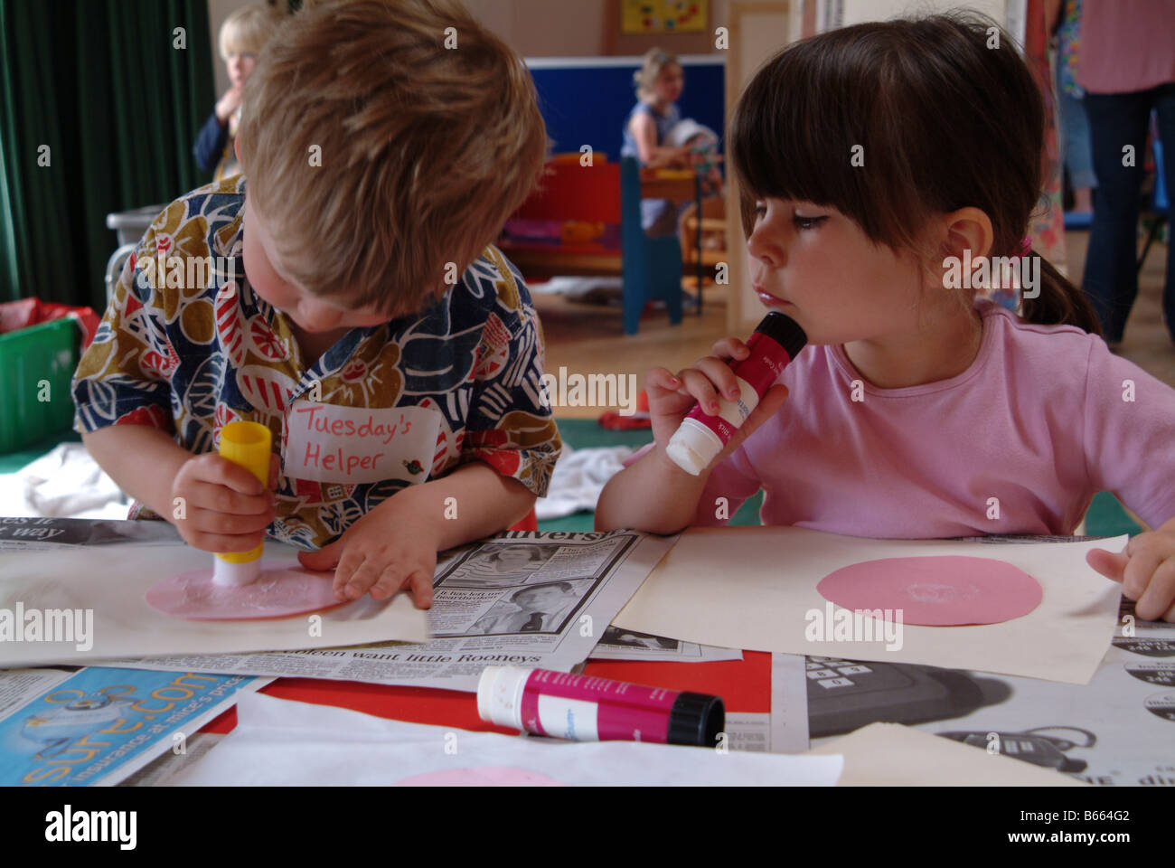 Children glueing pictures at nursery - Stock Image