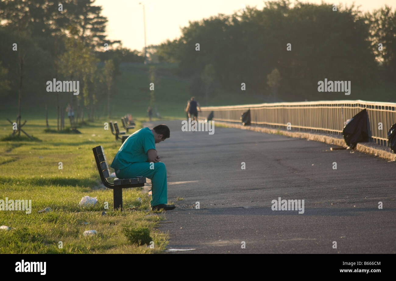 A medical doctor sitting on bench in a park - Stock Image