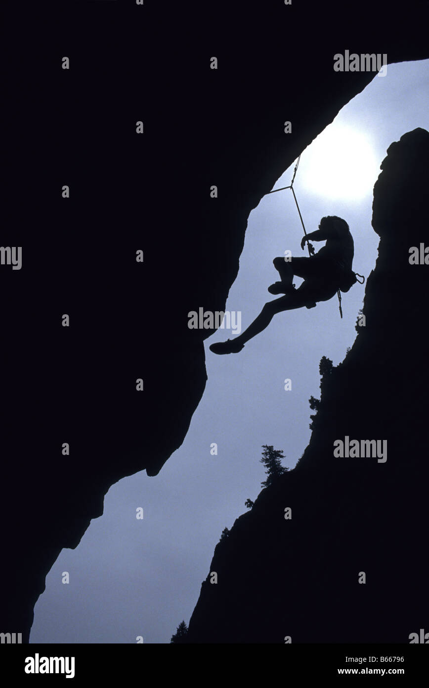 Silhouette of rock climber hanging from cliff face - Stock Image