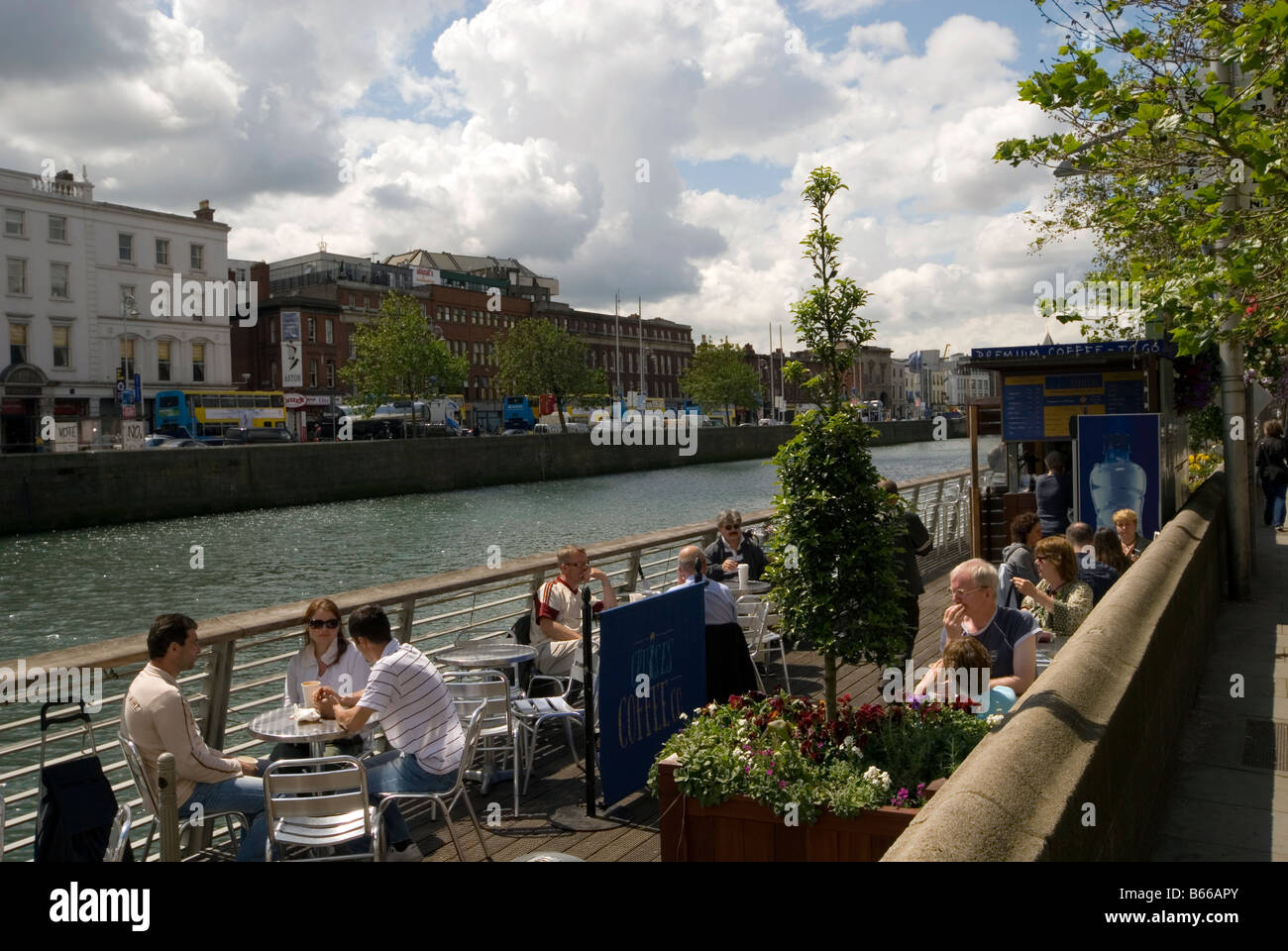 People drinking by River Liffey, Dublin, Ireland. - Stock Image