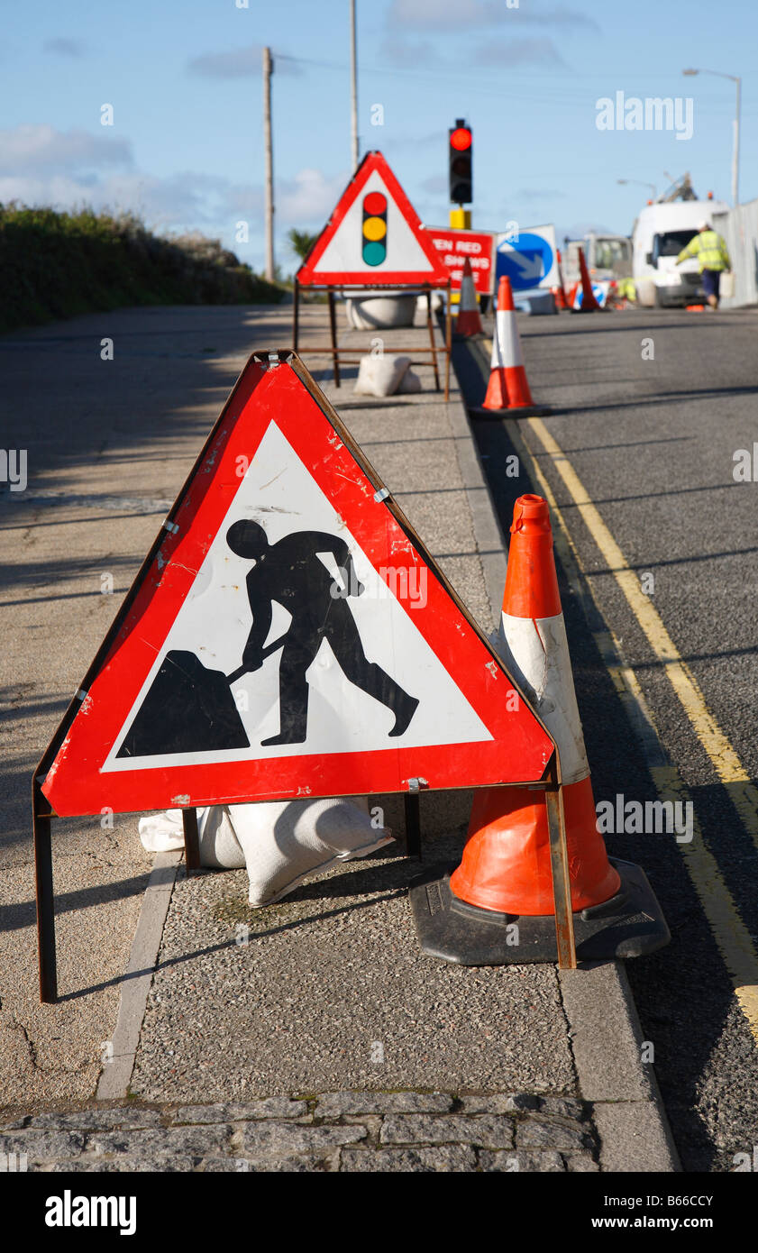 Road works sign with shallow focus and traffic lights in the distance. - Stock Image