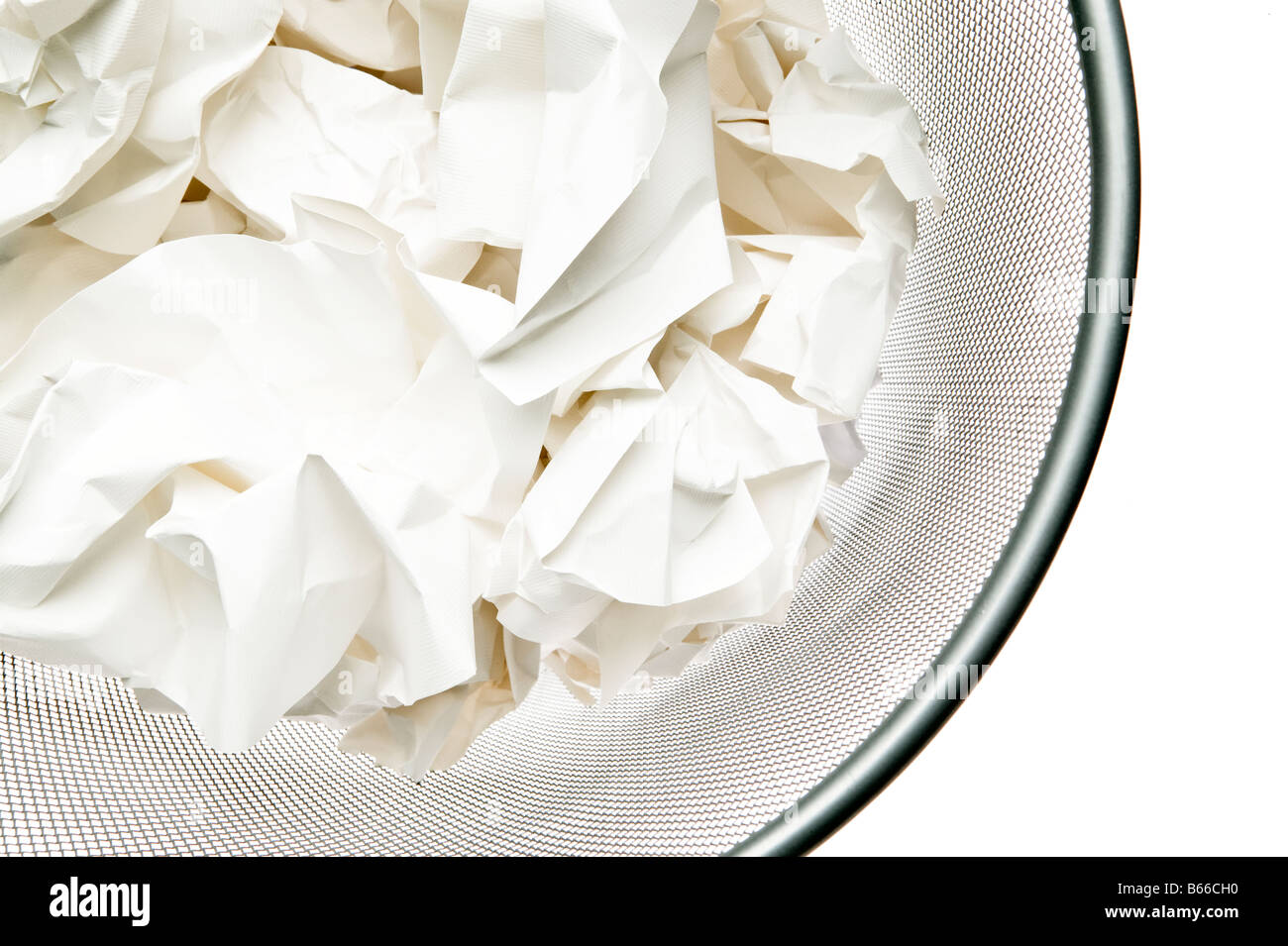 grey metal waste paper basket filled with crumpled white paper Stock Photo