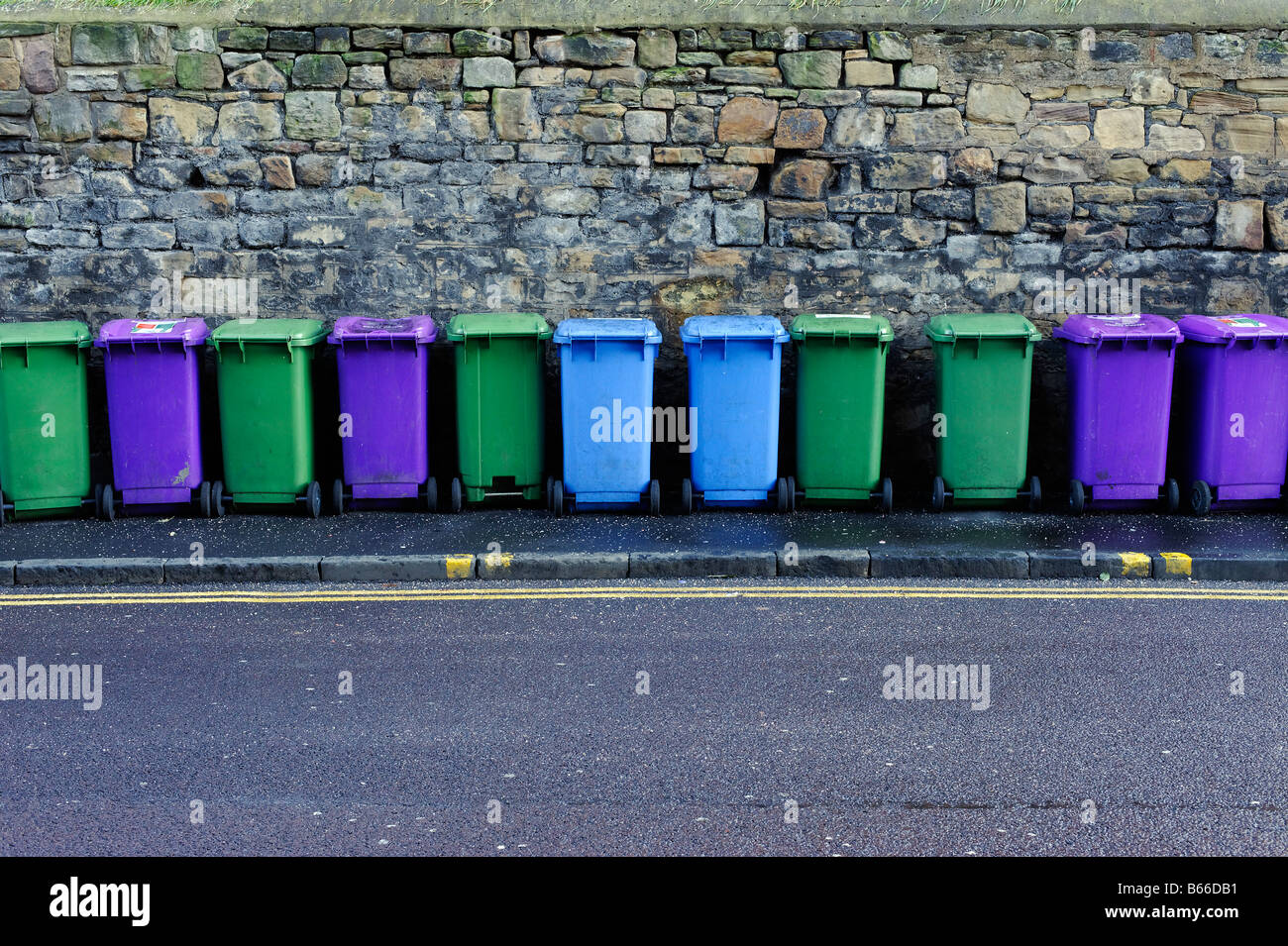 Line of multicoloured recycling bins lined up in front of a stone wall Stock Photo