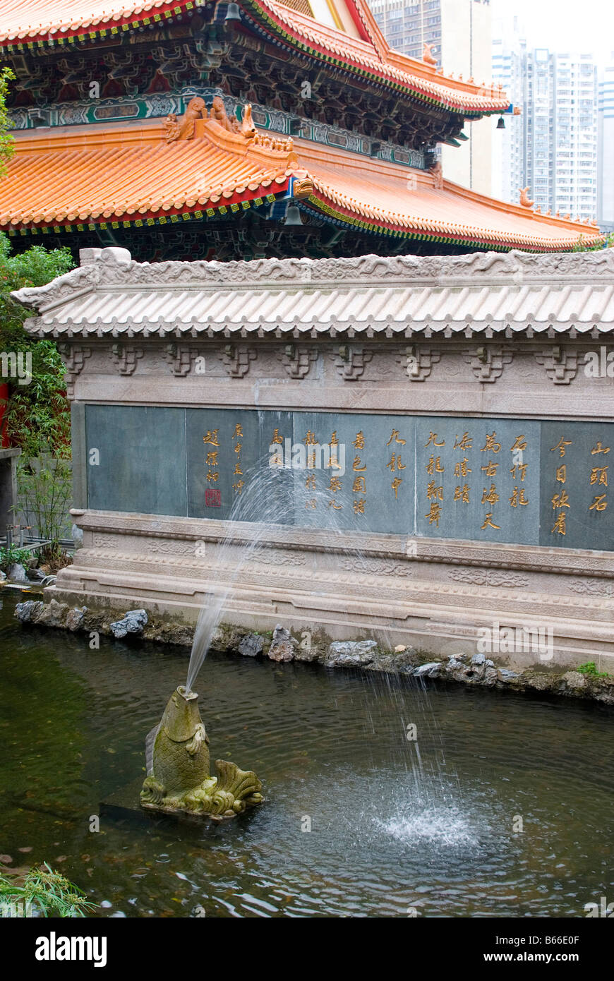 Stone carved carp fountain sprays in ponds by the nine dragons wall in the Good Wish Gardens at Wong Tai Sin Temple. - Stock Image