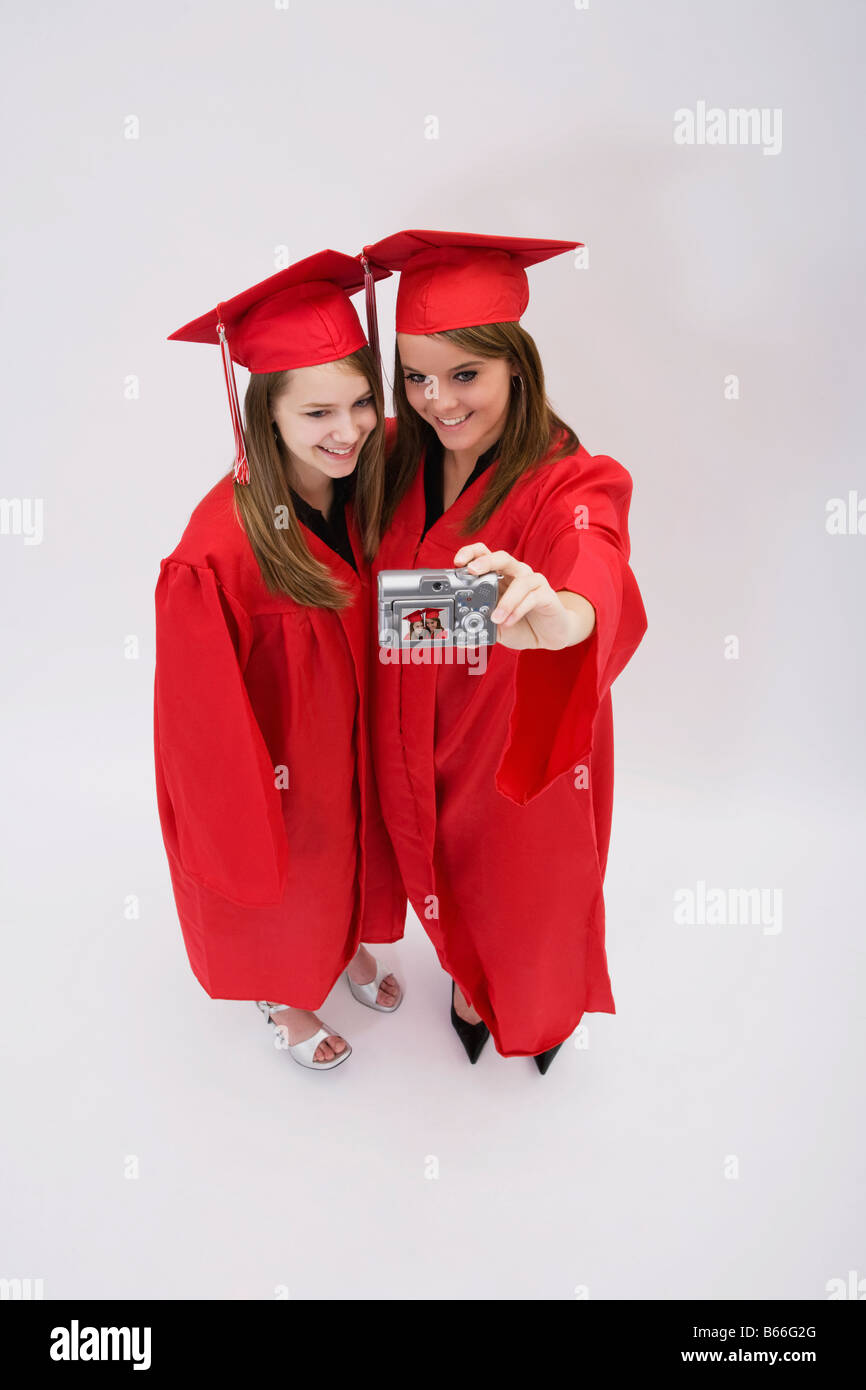 b7142b0c808 Studio portrait of two girls in red graduation gowns Stock Photo ...