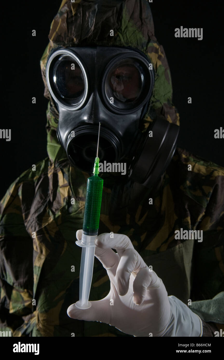 Soldier in respirator and protective suit inspects hypodermic of green liquid - Stock Image