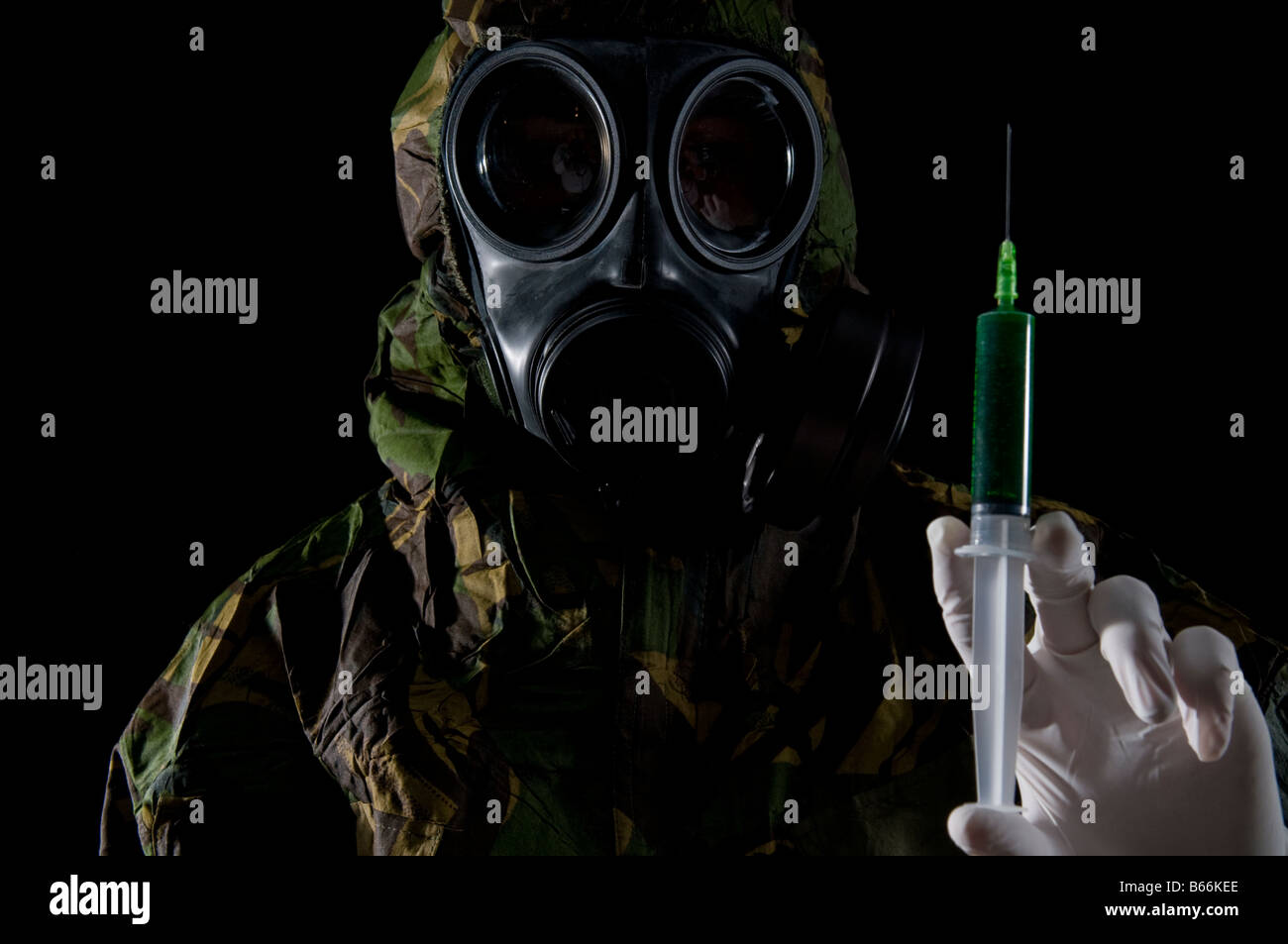 Soldier in respirator and protective suit inspects hypodermic of green liquid Stock Photo