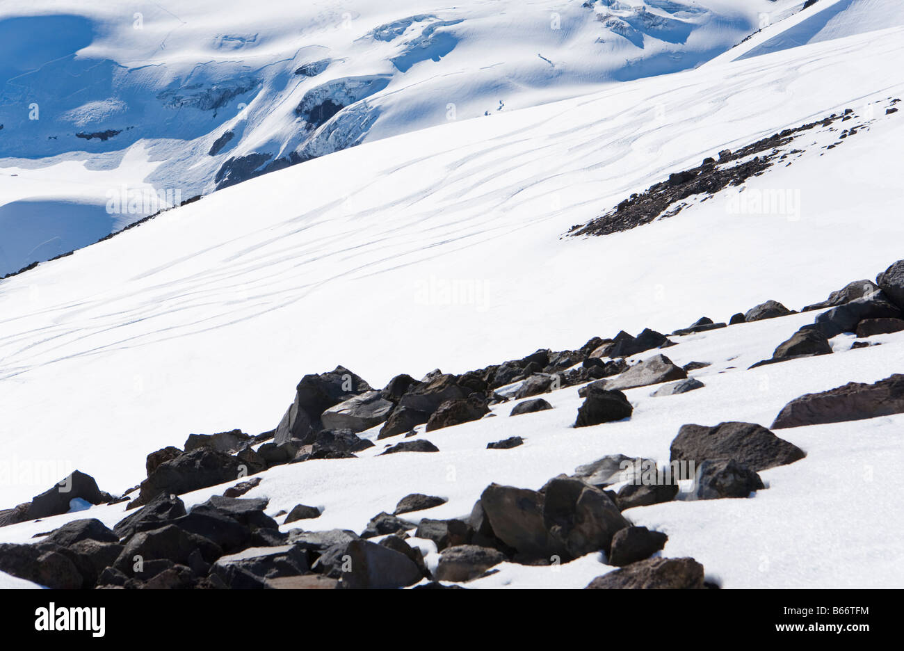 Melting snow revealing rocks on Mt Rainier with ski tracks in the distance - Stock Image