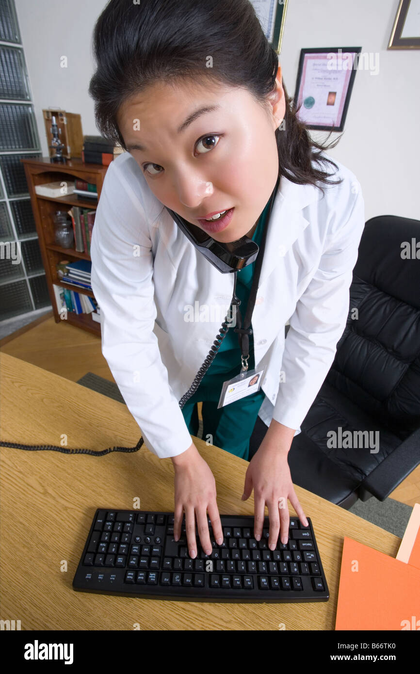 Busy doctor talking on phone and using her computer. - Stock Image