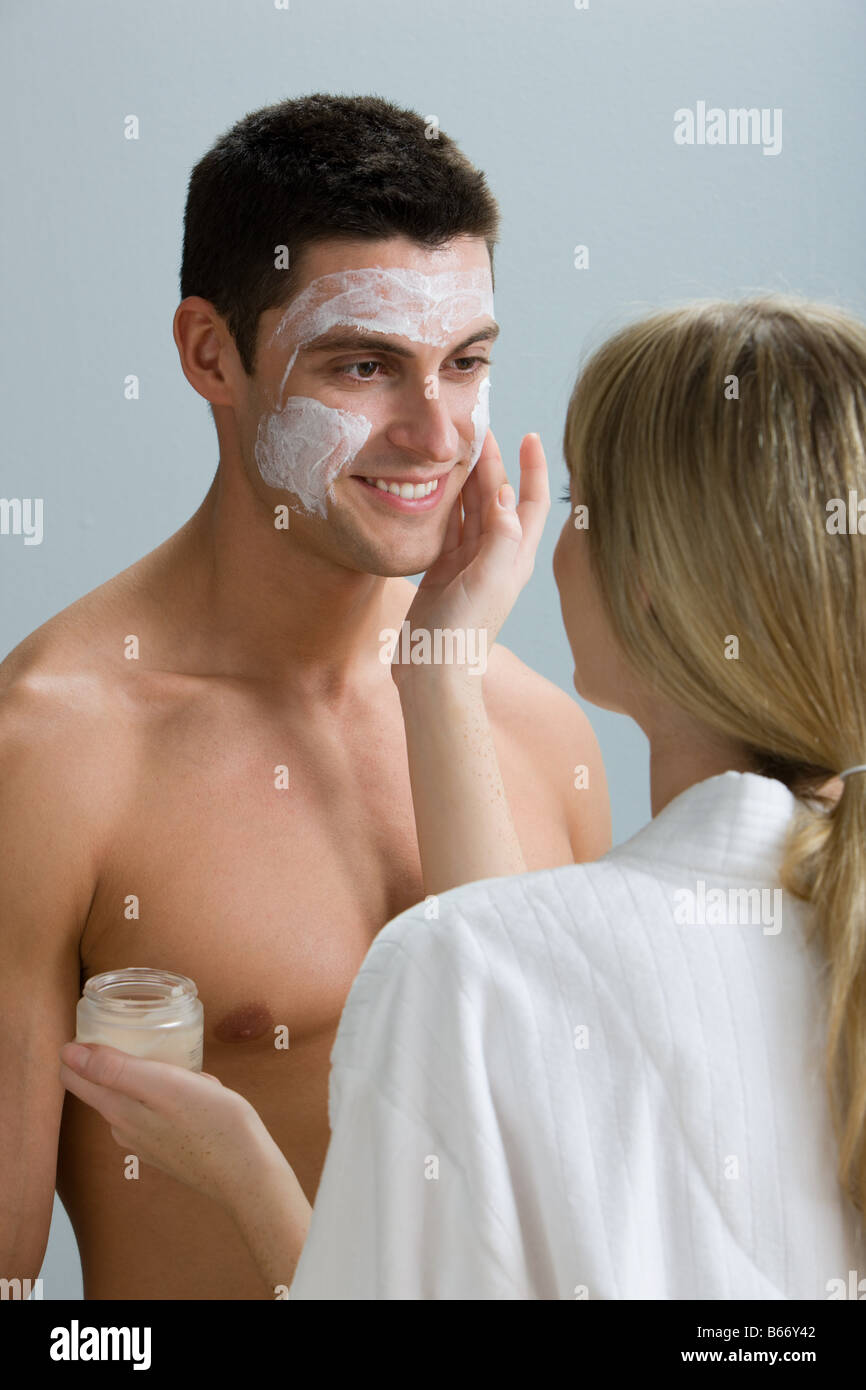 A woman applying face mask to a mans face - Stock Image