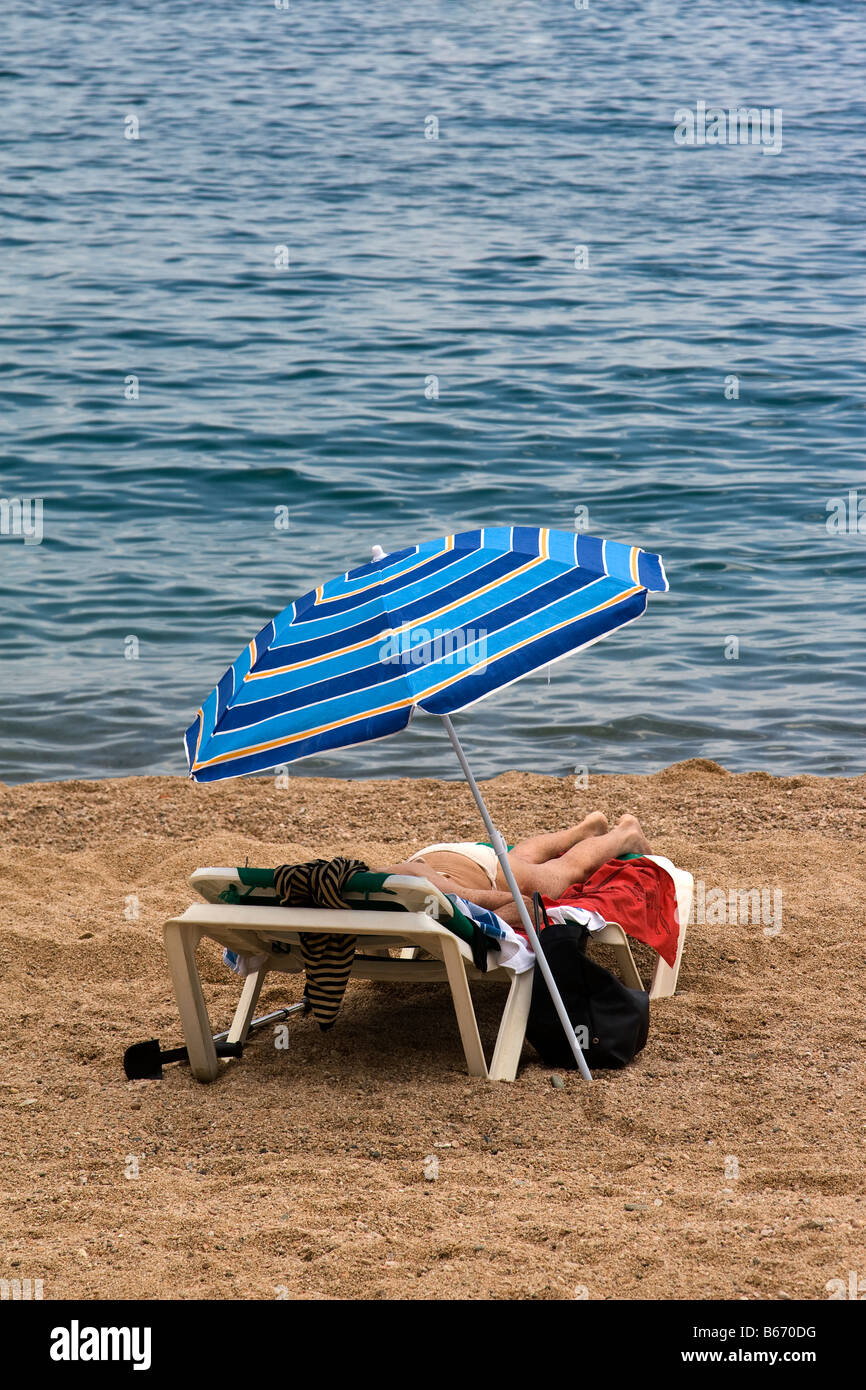 sunbather on a beach - Stock Image