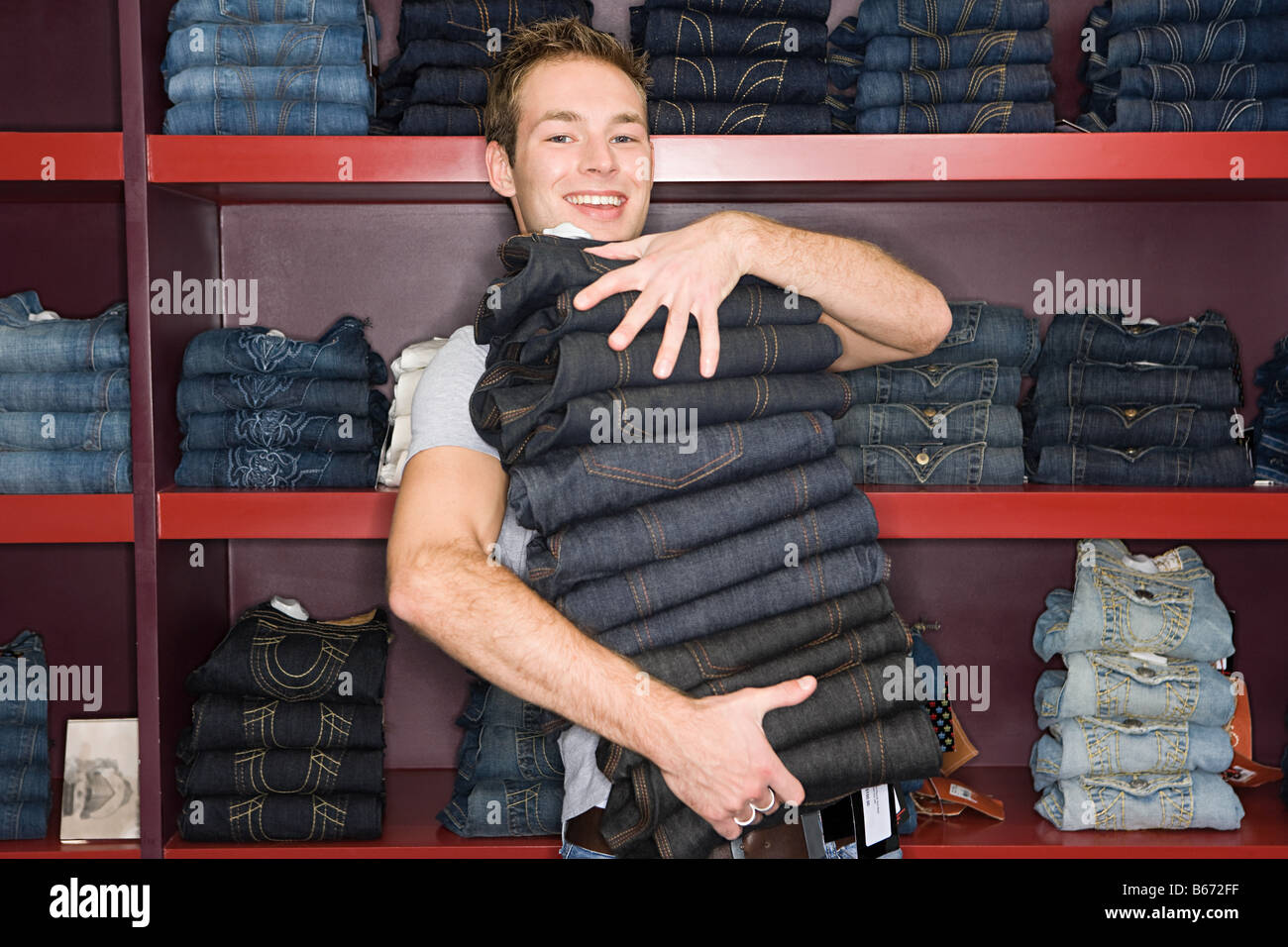 Man holding a stack of jeans - Stock Image
