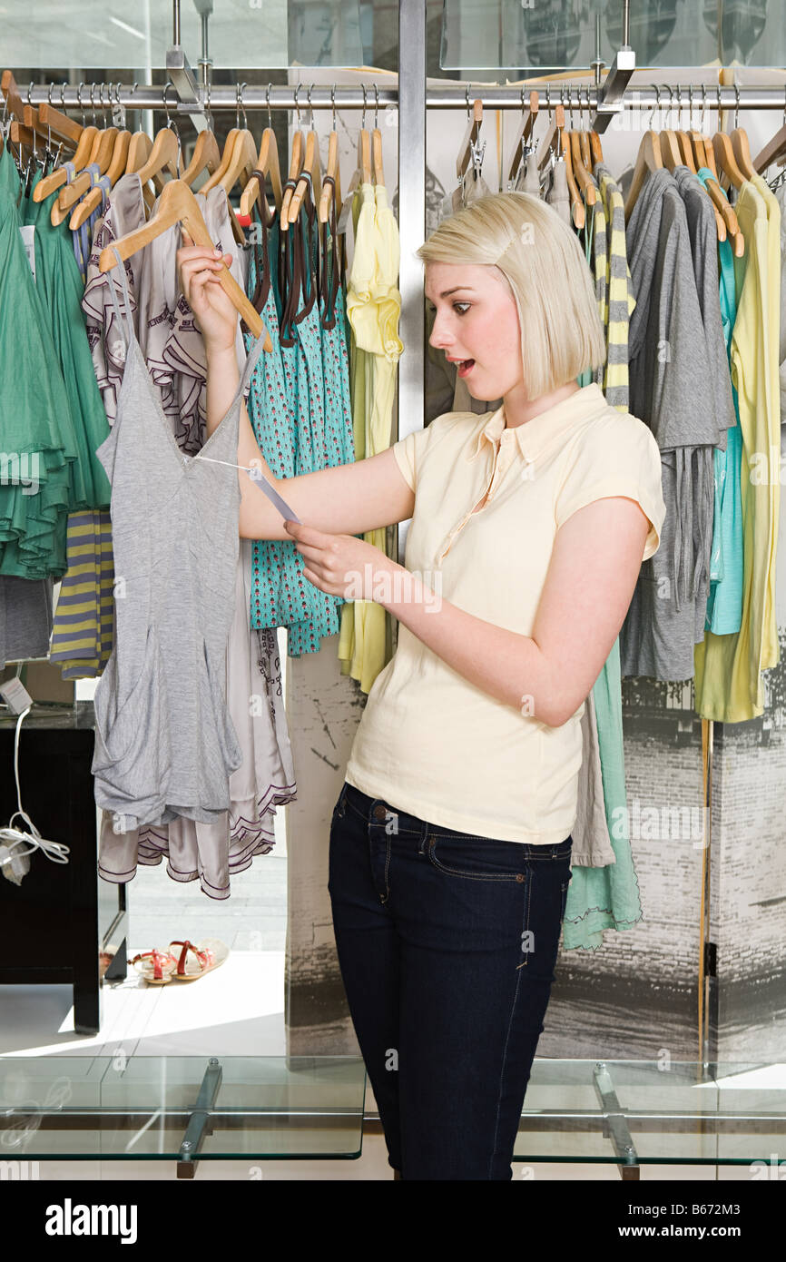 Woman shocked at clothes price - Stock Image