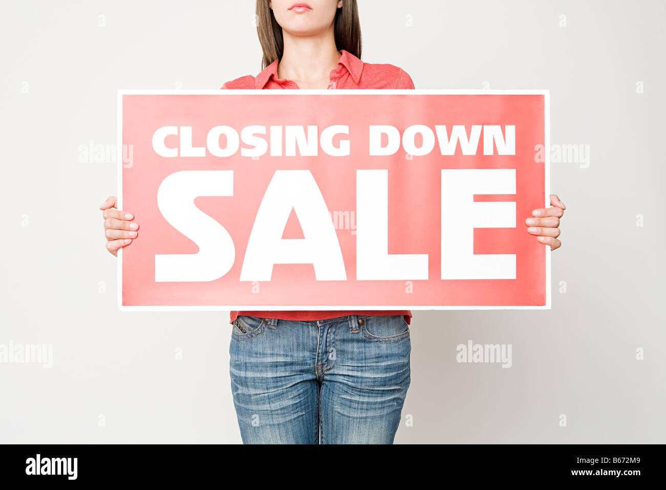 Woman holding a closing down sign - Stock Image