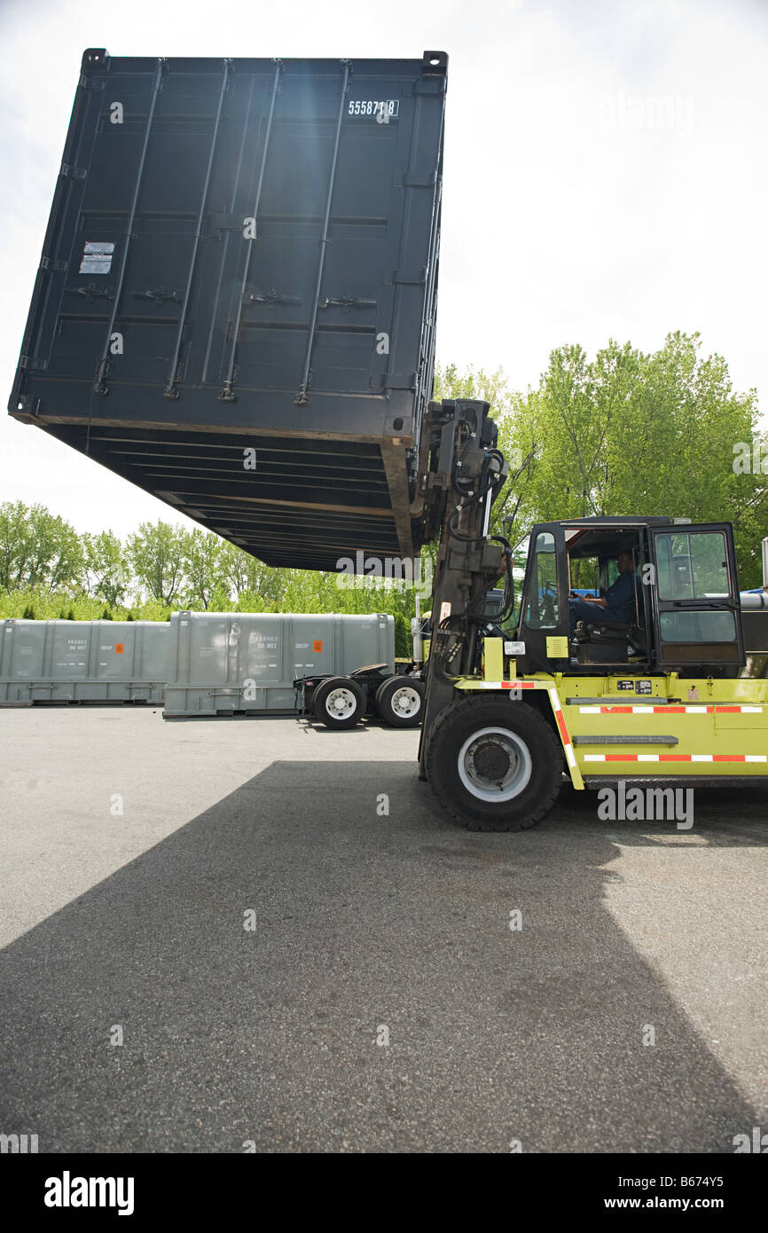 Forklift truck lifting cargo container - Stock Image