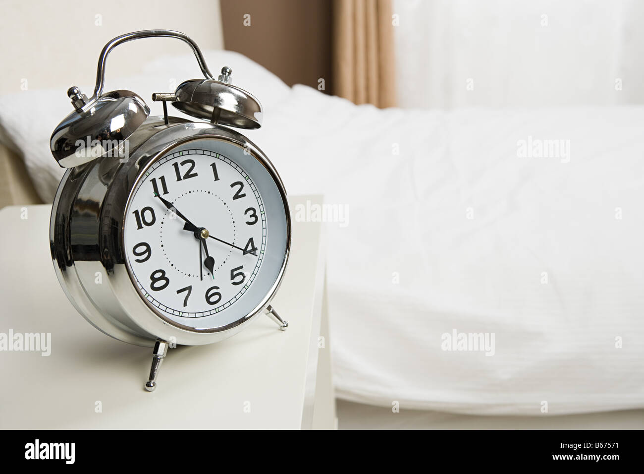 Alarm clock by bed Stock Photo