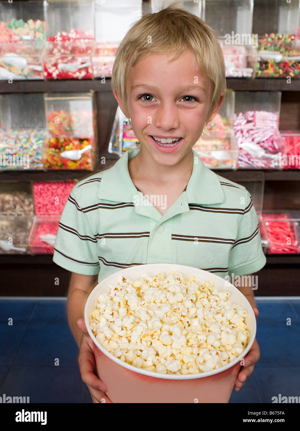 Portrait of a boy holding a tub of popcorn - Stock Image