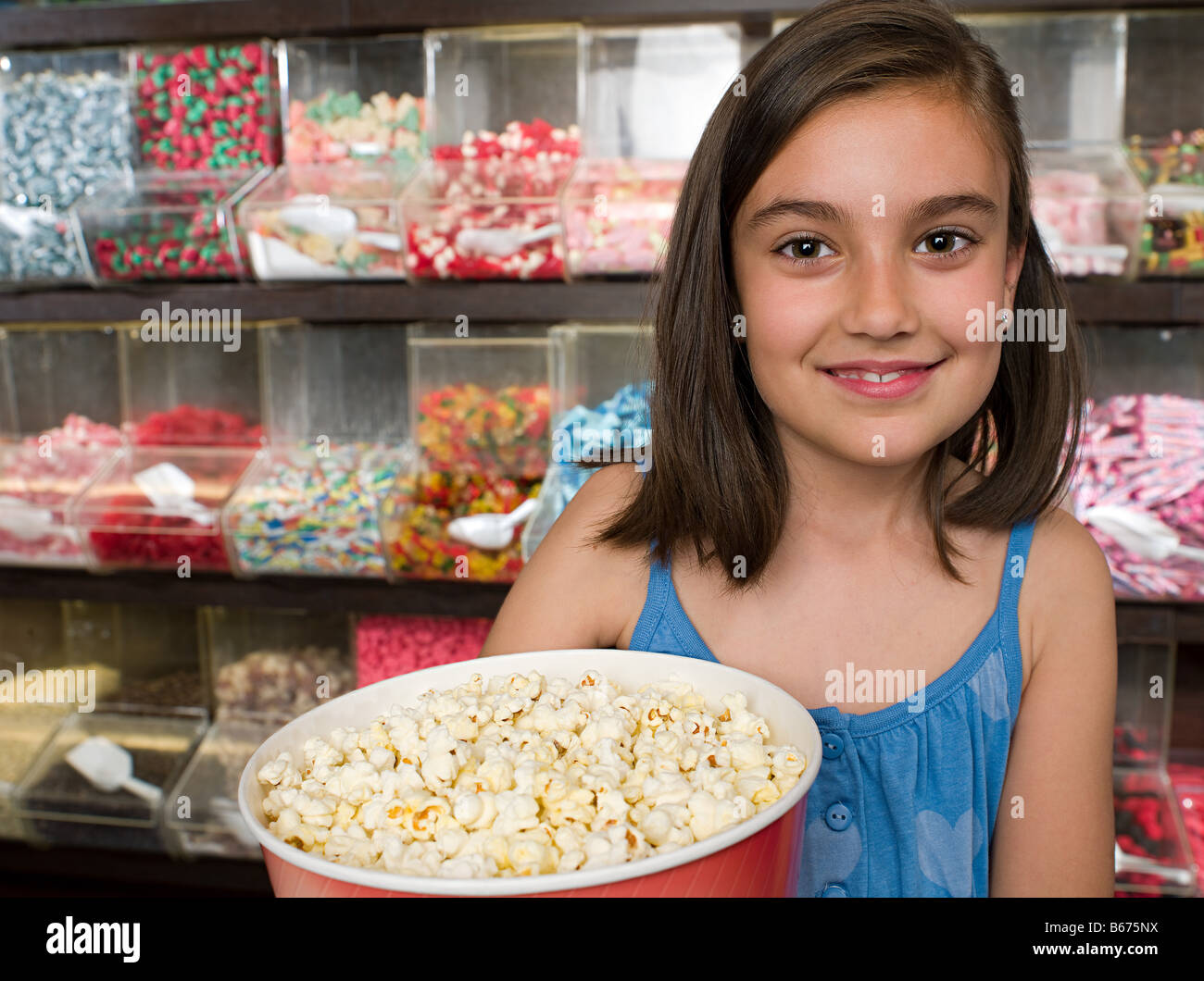 Girl holding a tub of popcorn - Stock Image