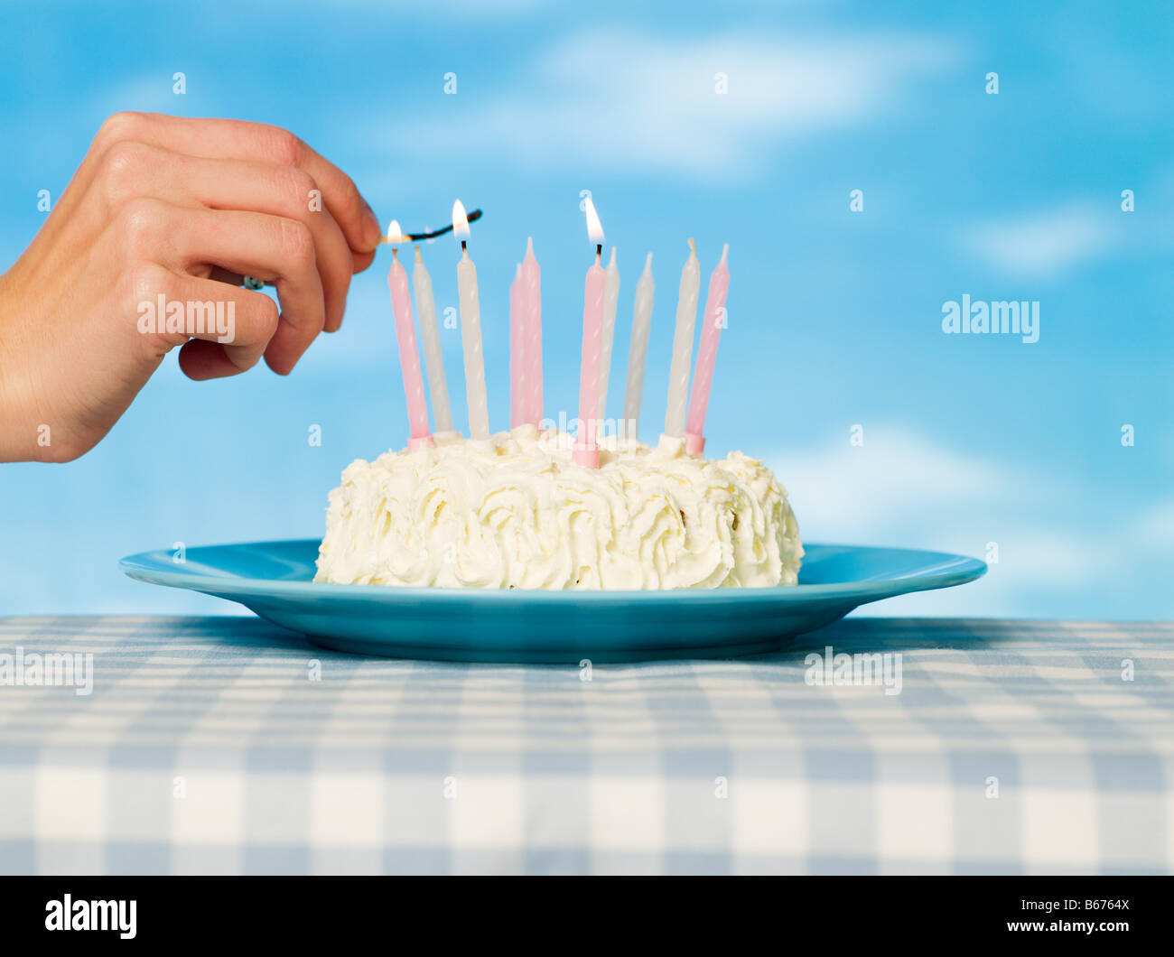 A person lighting matches on a cake - Stock Image